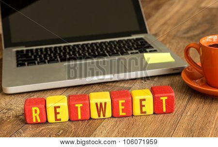 Retweet written on a wooden cube in front of a laptop