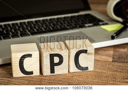 CPC (Cost Per Click) written on a wooden cube in front of a laptop