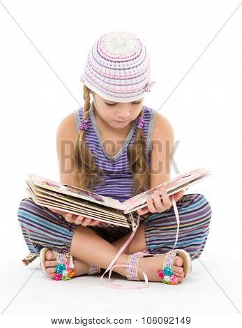 Little Girl Looking Album Sitting On The Floor