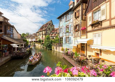 Collar, France- July 13, 2015: Tourist riding boat along canal in Colmar, Alsace, France. The town is situated along the Alsatian Wine Route and considers itself to be the capital of Alsatian wine.