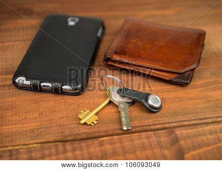 Leather Purse, Phone Pouch And Keys On A Wooden Table Background