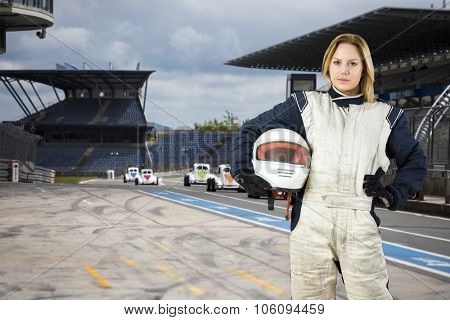 Female race car driver, holding her helmet under her arm, standing in the pits lane of a race track circuit