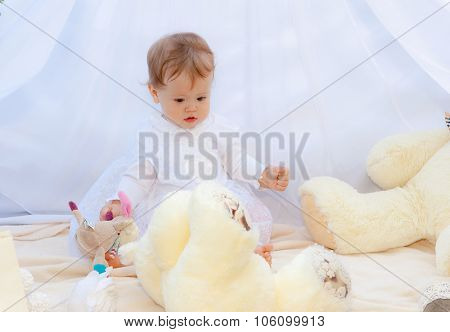 Baby playing in a park near the tents of baldachin