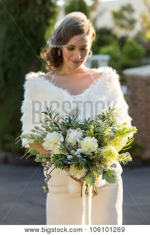 Beautiful bride holding her bouquet on her winter wedding