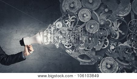 Hand of businessman with megaphone and gears mechanism