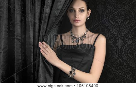 Beautiful woman with jewellery on dark background poster