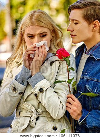 Betrayal and forgiveness couple. Girl is crying with handkerchief on outdoor. Withered rose as a symbol of lost love poster