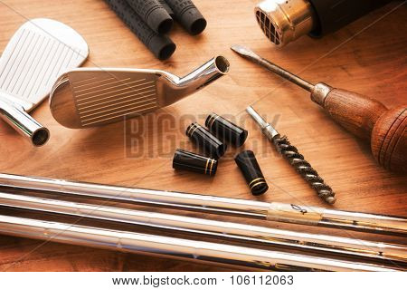 Custom golf clubs or club modifications. Golf club components on a work desk or work bench. grips, shaft, ferrules and, iron head. Focus is on black ferrule parts. Shallow depth of field. poster
