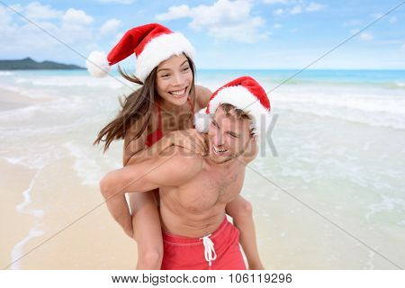 Christmas couple having fun on beach vacation doing piggyback. Laughing funny young friends playing on beach during winter holidays wearing santa hats. Multiracial people
