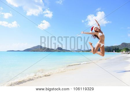 Happy Christmas vacation - girl jumping of joy and surprise on perfect white sand beach for winter holidays. Young woman wearing santa hat arms raised of happiness during vacations.