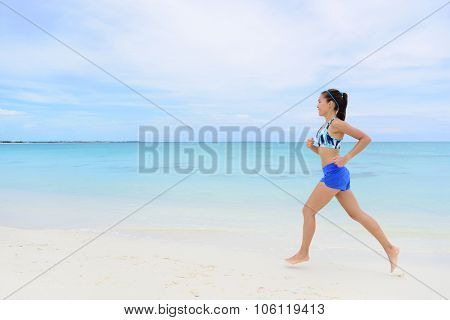 Healthy and active lifestyle running woman jogging on beach. Full length young female adult doing morning cardio workout barefoot in white sand and turquoise ocean background. poster