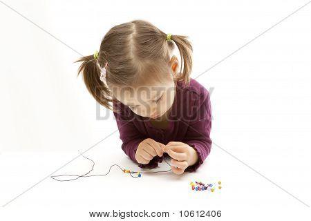 Cute Little Girl Beading On White Background