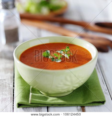 tomato soup in green bowl with herb garnish on rustic table