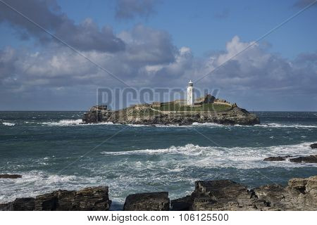 Godrevy lighthouse with waves on rocks, cornwall, uk