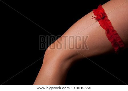 Woman leg with red scarf on black background