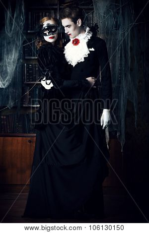 Gorgeous couple of vampires dressed in medieval clothing dancing in the old abandoned castle. Halloween. Carnival.  poster