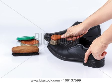woman's hand polishing black leather shoes with shoe brush on white background poster