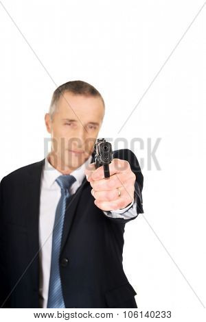 Serious mafia agent aiming by handgun. poster