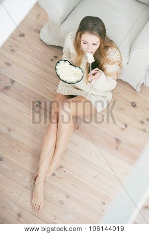 Beautiful sad woman eating ice cream at home.