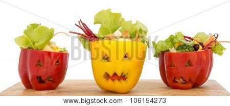Colorful Halloween Food With Sweet Bell Peppers With Cutout Faces In Like Halloween Jack-o-lanterns