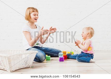 Baby girl and her older sister clapping hands