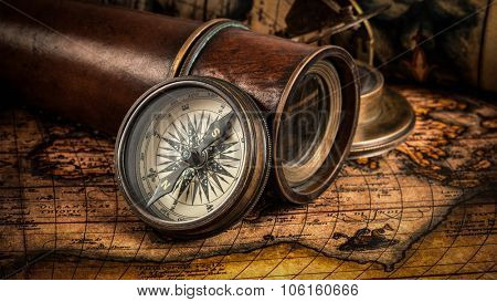 Travel geography navigation concept background - panorama of old vintage retro compass with sundial, spyglass and rope on ancient world map