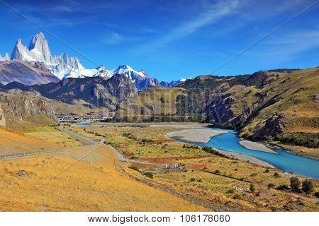 Vertiginous landscape in the Chilean Andes. The road between turned yellow hills and river goes to snow-covered black rocks. Patagonia