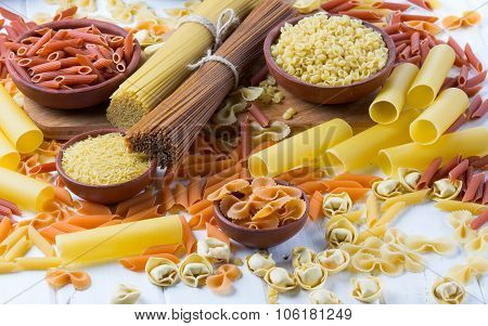 Variety of types and shapes of dry italian pasta. background