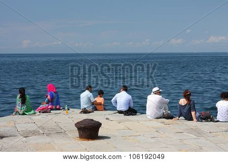 Trieste, Italy - August 18, 2015: Group Of Tourists  Seats On Molo Audace