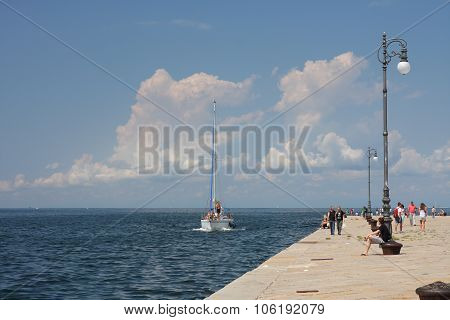 Trieste, Italy - August 18, 2015: Group Of Tourists  Walking  On Molo Audace And Arriving Sailboat