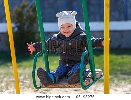 Fearless Kid Swinging On The Swing Taking Hands Free