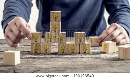 Front View Of A Man Arranging Wooden Blocks With Hand Drawn Yellow Lightbulb In A Random Structure