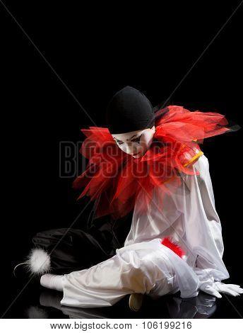 Sad Clown or Pierrot sitting on the black floor