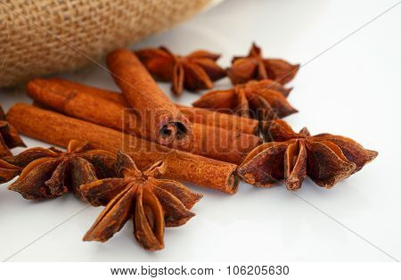 Cinnamon and star aniseed sticks on white.