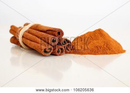 Cinnamon sticks and powder on white.