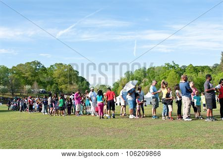 Parents And Kids Wait In Long Line For Festival Ride