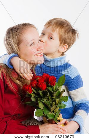 Cute boy giving red roses to his mother