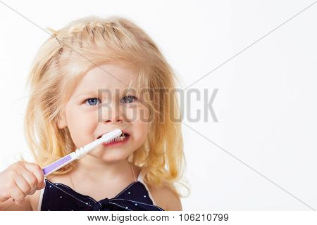 Beautiful blonde haired girl with toothbrush in her hand on whit