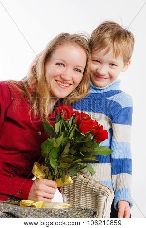 Laughing mother and her son with bouquet of roses