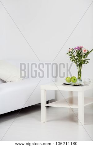 Small table with flowers and fruits