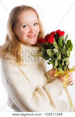 Lovely woman in knitted sweater holding bouquet of red roses