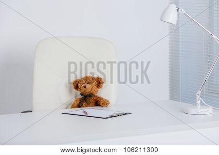 Small teddy bear sitting at big desk