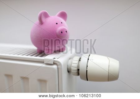Pink piggy bank on radiator. Energy saving concept.