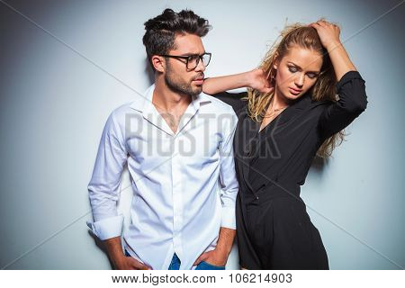 male posing with hands in pockets looking at blonde woman in black dress fixing her hair while looking down