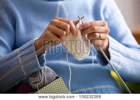 Female hands with knitting needles while knitting. Knitting therapy