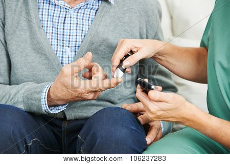 Blood glucose monitoring on finger of senior man with diabetes