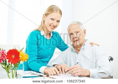 Granddaughter and grandfather solving crossword puzzle together at home