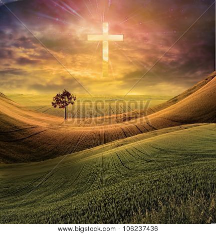 Cross radiates light in sky over beautiful landscape