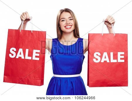 Cheerful shopaholic with toothy smile holding two paperbags announcing sale