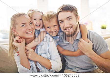 Cute siblings embracing their joyful parents poster